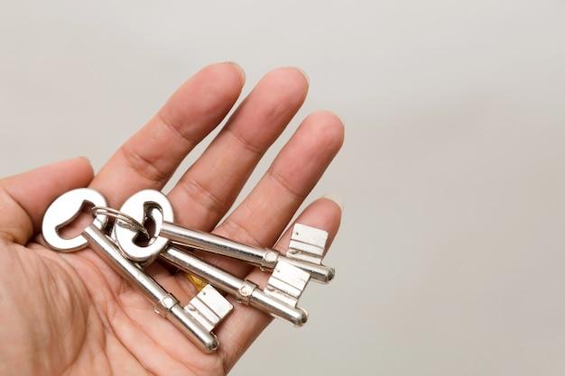 Main tenant la clé isolée. éclairage de studio.
