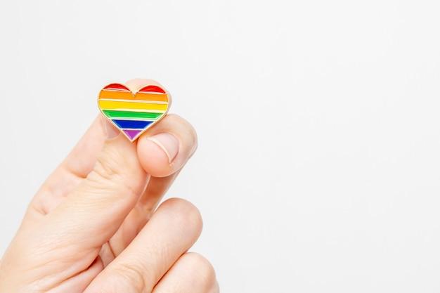 Main tenant le coeur du symbole de la fierté gay arc-en-ciel comme concept de droits lgbt, espace copie