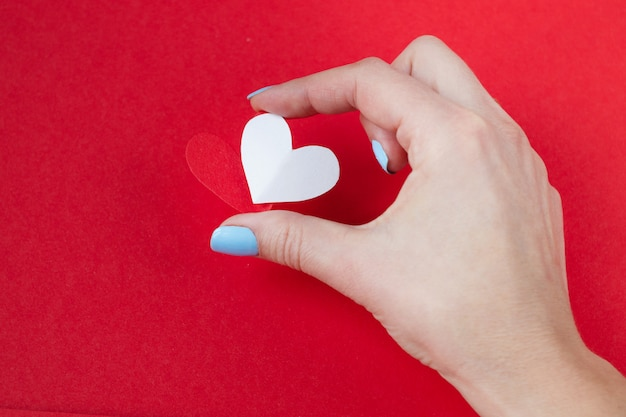 Main tenant un coeur rouge et blanc sur fond rouge. fond pour la saint valentin