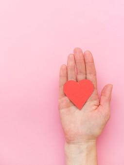 Une main tenant un coeur rouge sur fond rose