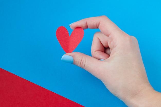 Main tenant un coeur rouge sur un fond rouge et bleu. fond pour la saint valentin