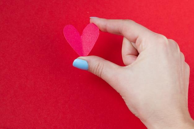 Main tenant un coeur rouge sur fond rouge. fond pour la saint valentin