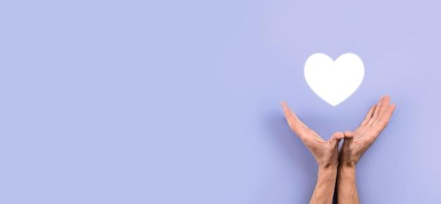 Main tenant le coeur rouge avec le symbole de la croix blanche. fond de carte du monde. concept de soins de santé, d'assurance maladie, de bienfaisance et de médecine. espace de copie.