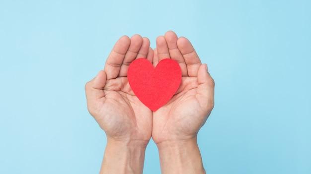 Main tenant un coeur de tissu rouge sur fond bleu.