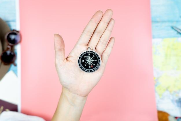 Main tenant un compas avec accessoires pour concept de voyage