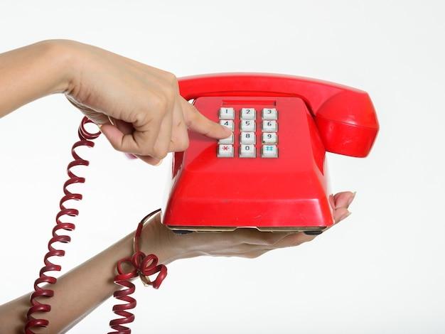 Main tenant et composer le vieux téléphone contre le mur blanc