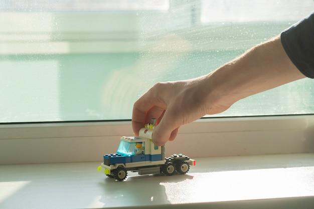 Une main tenant un constructeur de voiture jouet, faite de briques de détails, de créativité et d'apprentissage