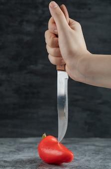 Main tenant un couteau et du poivron rouge.