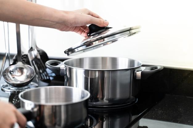 Main tenant le couvercle au-dessus de la casserole dans la cuisine