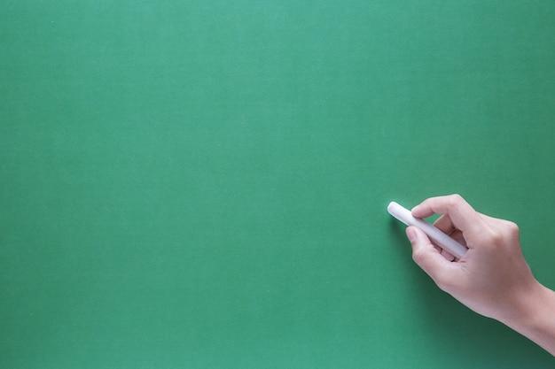 Main tenant la craie avec fond de tableau de craie verte