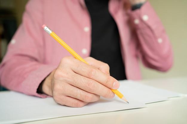 Main tenant un crayon et dessin sur papier