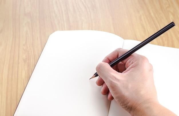 Main tenant le crayon noir écrit sur un cahier ouvert blanc sur la table en bois, modèle d'affaires