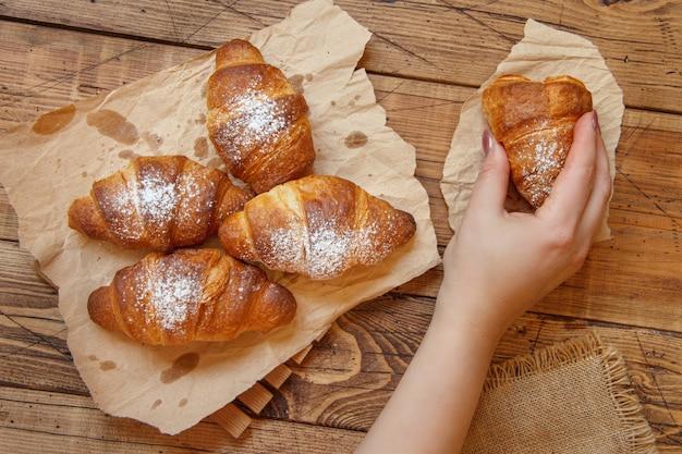 Main tenant un croissant croustillant frais français à partir d'une vue de dessus de table en bois