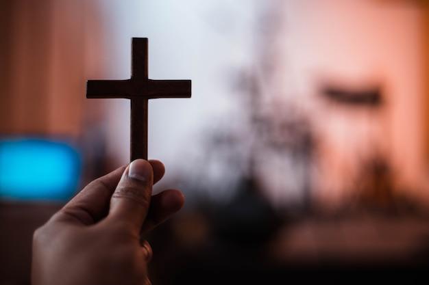 Main tenant une croix en bois avec arrière-plan flou.