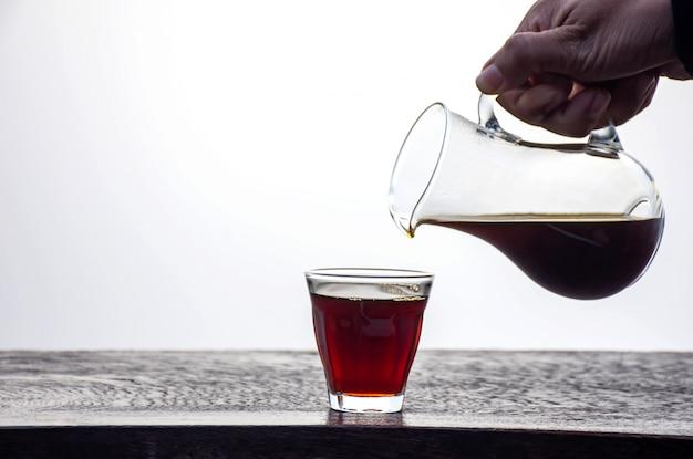 Main tenant une cruche de café noir versé dans un verre sur une table en bois.
