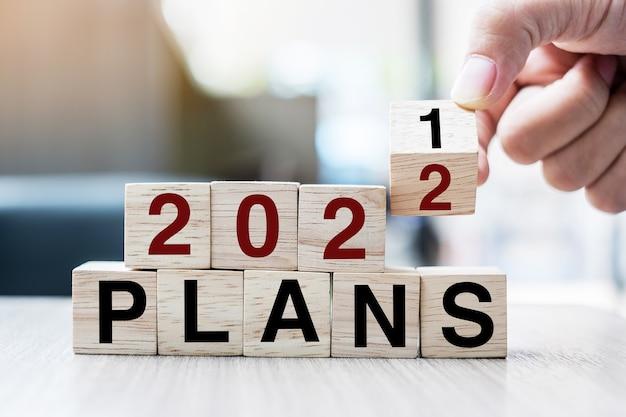 Main tenant un cube en bois avec bloc à bascule 2021 à 2022 mot des plans