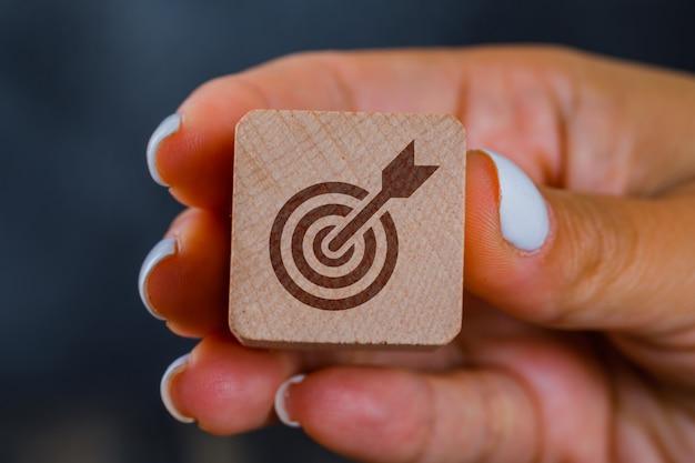 Main tenant un cube en bois avec cible