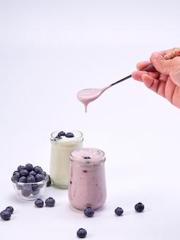 Main tenant une cuillère avec du yogourt aux myrtilles