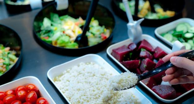 Main tenant la cuillère avec les larmes de job bouillies au bar à salade. buffet de bar à salades au restaurant. buffet de salades fraîches pour le déjeuner ou le dîner. la nourriture saine. restauration de nourriture. service de banquet. la nourriture végétarienne.