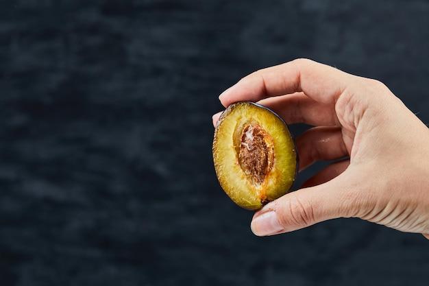 Main tenant une demi-coupe de prune sur fond noir.