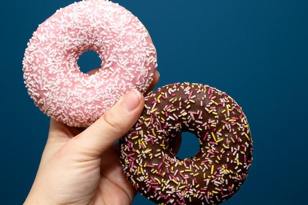 Main tenant deux un délicieux beignet coloré avec des paillettes, le concept de sucre rose et brun