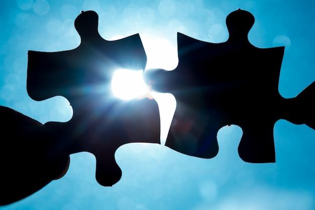 Main tenant deux pièces de puzzle