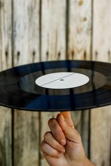 Main tenant un disque vinyle sur fond en bois