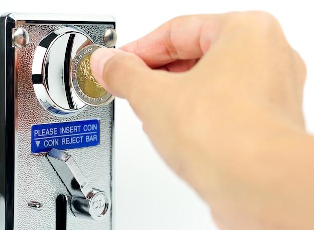 Main tenant un distributeur automatique de pièces sur fond blanc
