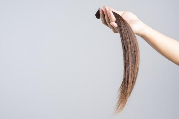 Main tenant un don de cheveux longs pour un patient atteint de cancer