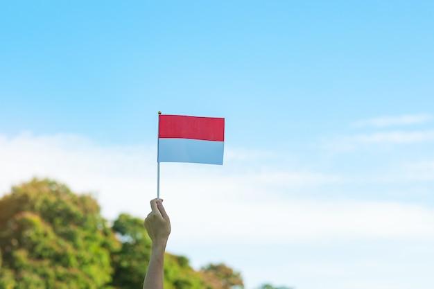 Main tenant le drapeau de l'indonésie sur fond de ciel bleu. jour de l'indépendance de l'indonésie, jour de la fête nationale et concepts de célébration heureuse