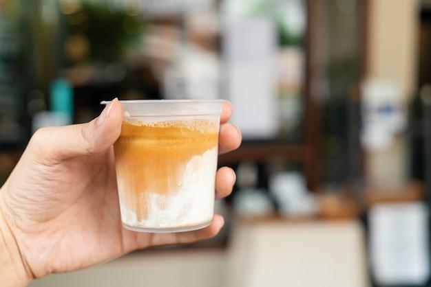 Main tenant du café sale dans un verre à emporter