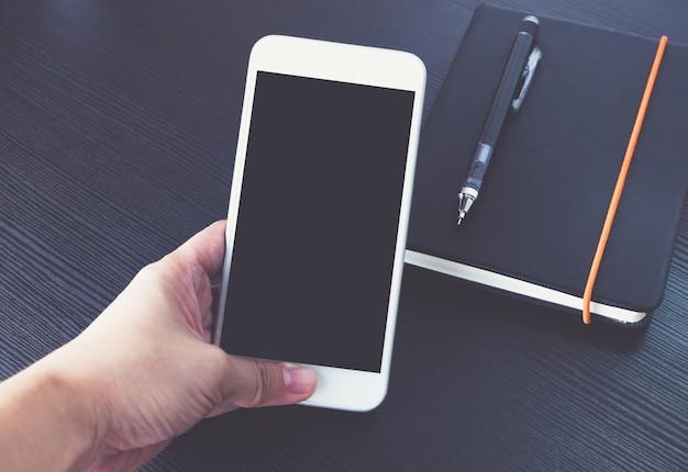 Main tenant un écran blanc de téléphone mobile sur un ordinateur portable noir sur un bureau en bois noir