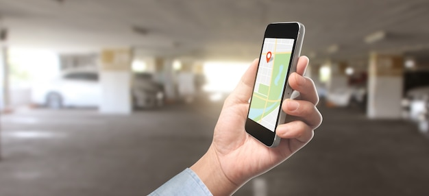 Main tenant l'écran tactile de l'appareil smartphone et carte gps navigator