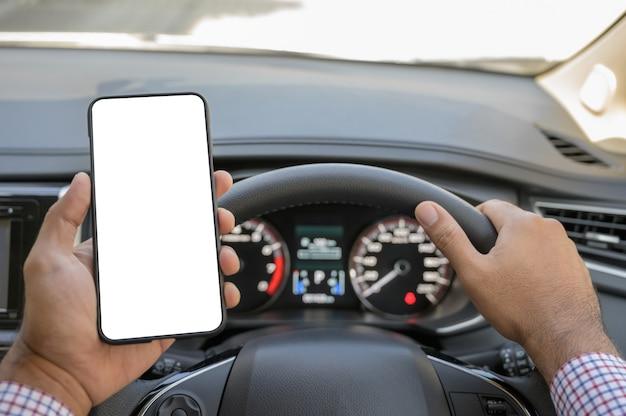 Main tenant un écran vide de smartphone en conduisant une voiture