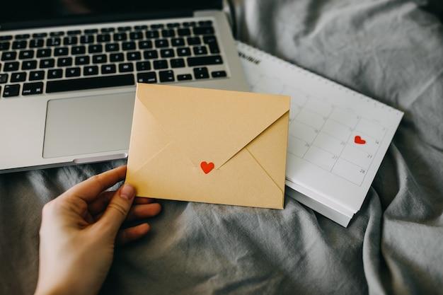 Main tenant une enveloppe jaune avec un cœur dessus sur fond d'ordinateur portable