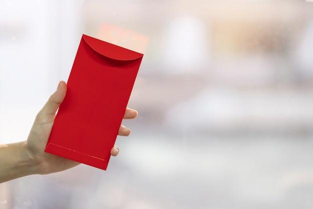 Main tenant une enveloppe rouge ou ang pao. concept de célébrations du nouvel an lunaire chinois