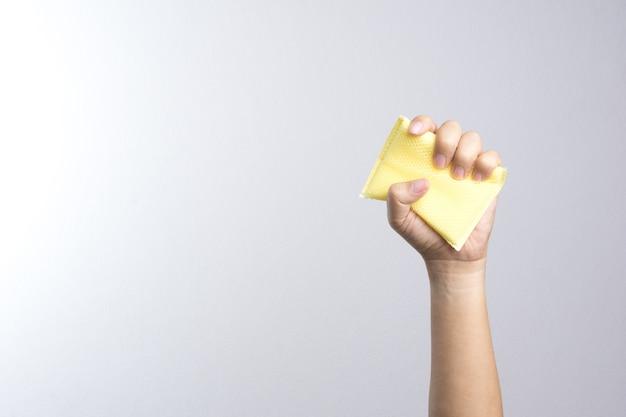 Main tenant une éponge de nettoyage