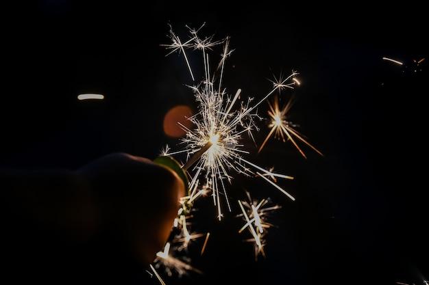 Main tenant l'étincelle de feu d'artifice exposée la nuit