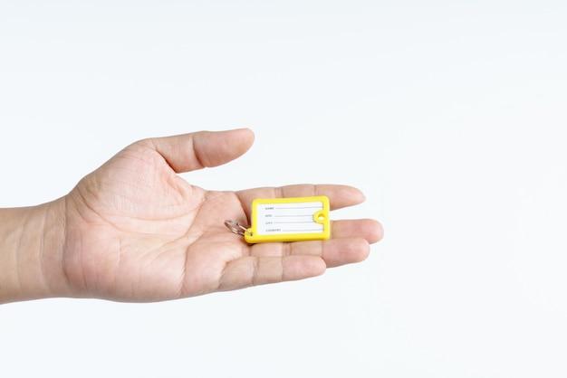 Main tenant une étiquette de bagage de voyage