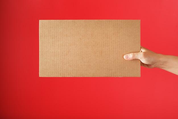 Main tenant une feuille de carton vierge sur une surface rouge
