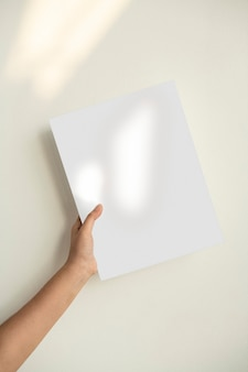 Main tenant une feuille de papier contre le mur vert