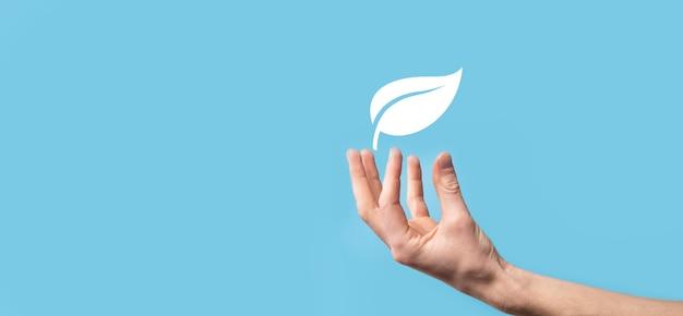Main tenant une feuille verte avec des icônes de sources d'énergie pour un développement durable et renouvelable. concept d'écologie. concept d'écologie de la technologie.
