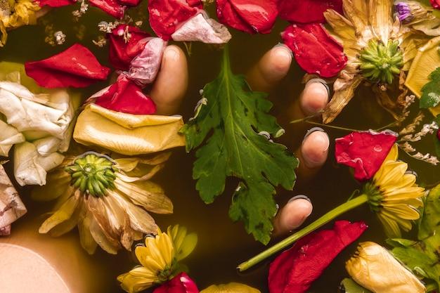 Main tenant des fleurs dans l'eau noire