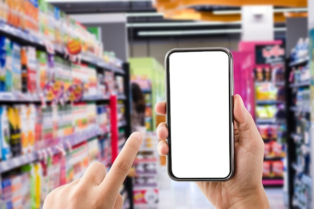 Main tenant une forme vierge de téléphone mobile avec un supermarché ou un centre commercial. achats en ligne ou concept de commerce électronique.