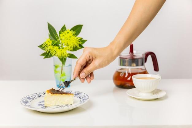 Main tenant la fourchette manger du gâteau au fromage basque brûlé avec une tasse de thé sur la table.