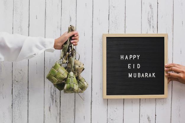Une main tenant un gâteau de riz en indonésie appelé ketupat et un tableau aux lettres dit joyeux aïd moubarak
