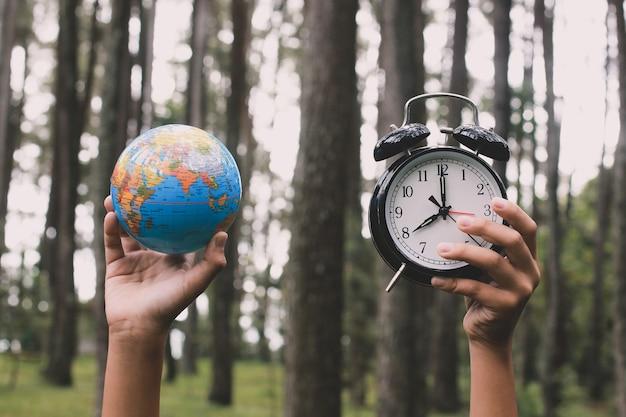 Main tenant le globe terrestre et réveil avec forêt floue
