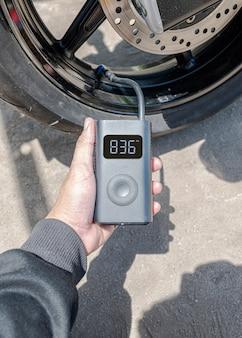Une main tenant un gonfleur portable gonfle un pneu de moto.
