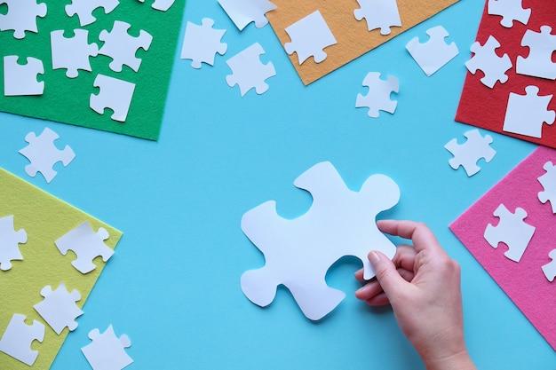 Main tenant une grande pièce de puzzle découpée dans du papier. mise à plat, vue de dessus sur arrangement créatif. éléments de puzzle et feuilles de feutre multicolores
