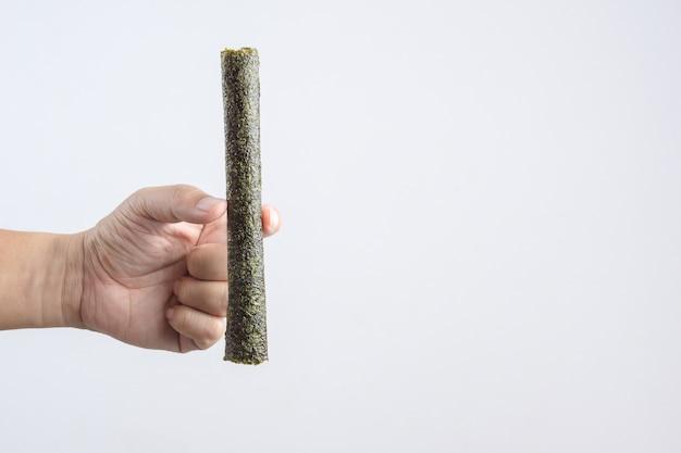 Main tenant un gros rouleau d'algues grillées croustillantes à la japonaise
